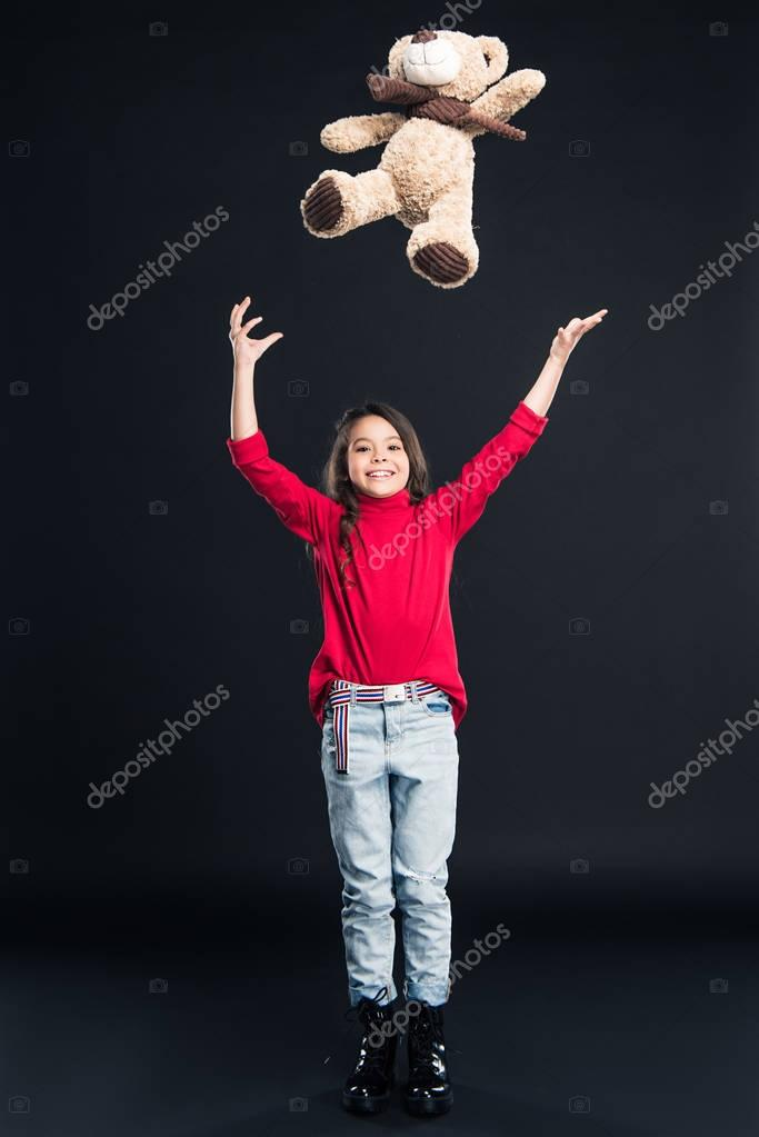 kid throwing up teddy bear