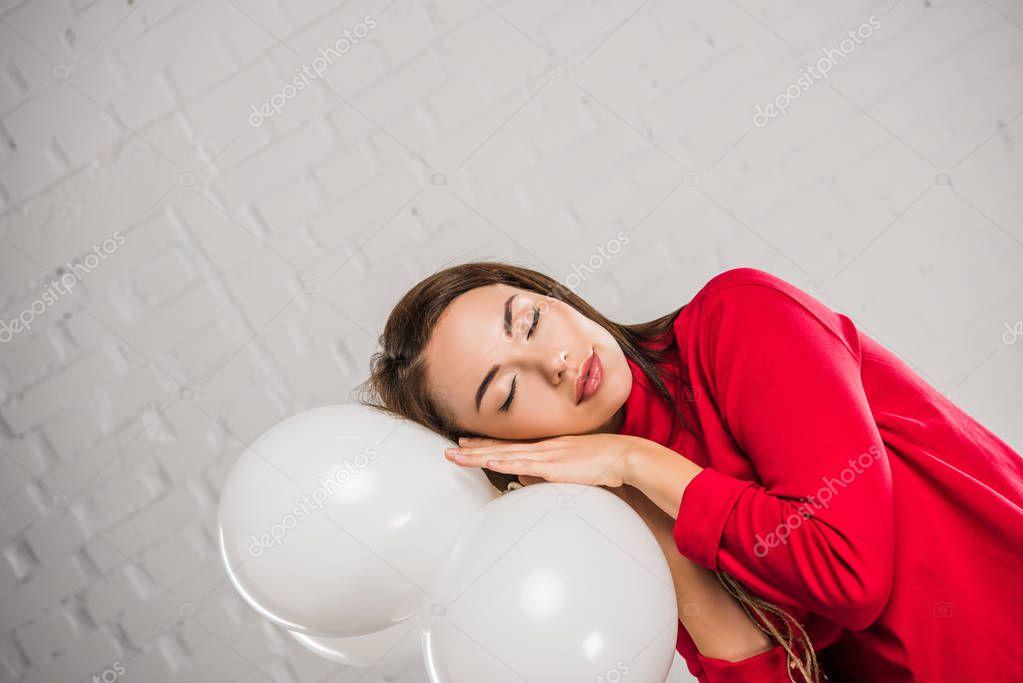 Woman sleeping on balloons