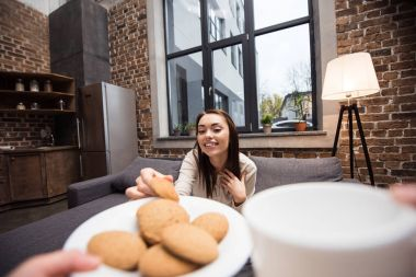 woman taking cookie