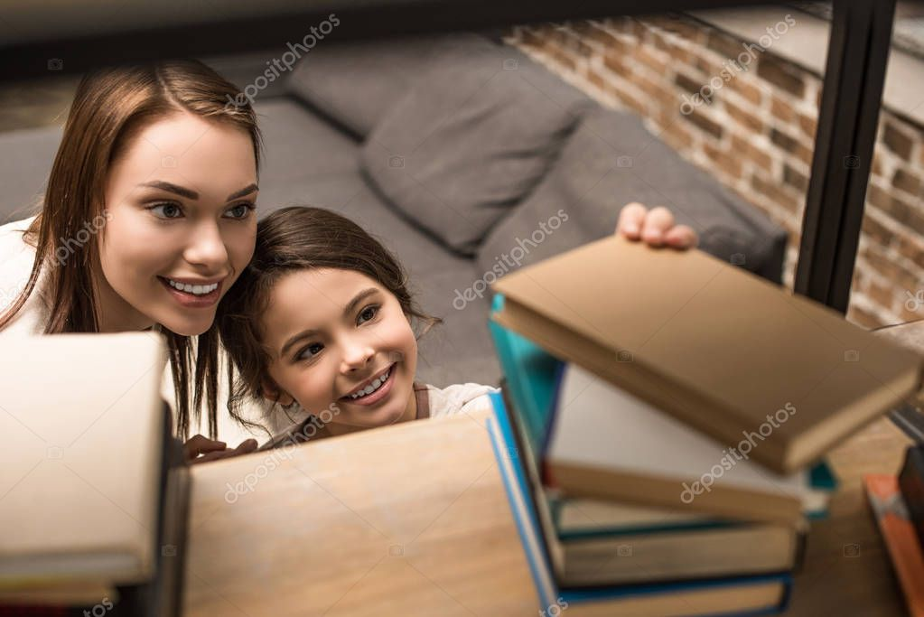 daughter taking book from bookshelf