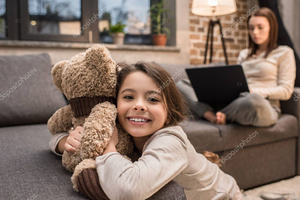kid playing with teddy bear