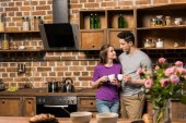 Fotografie couple looking at each other in kitchen and holding cups of coffee
