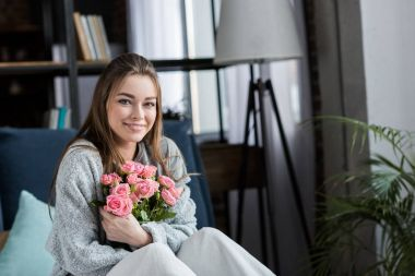 smiling girl hugging bouquet of pink roses and looking at camera, 8 march concept