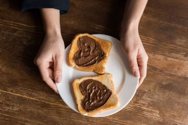 cropped image of girl holding plate with toasts with hearts, valentines day concept