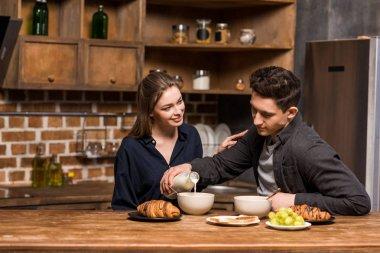 boyfriend pouring milk in plate at kitchen