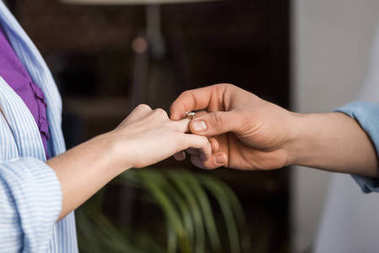 cropped image of boyfriend proposing girlfriend and wearing engagement ring