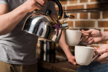 cropped image of boyfriend pouring coffee in cups