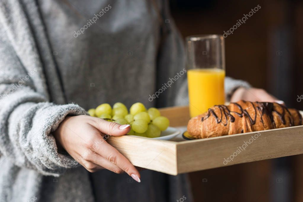 cropped image of girl holding tray with breakfast