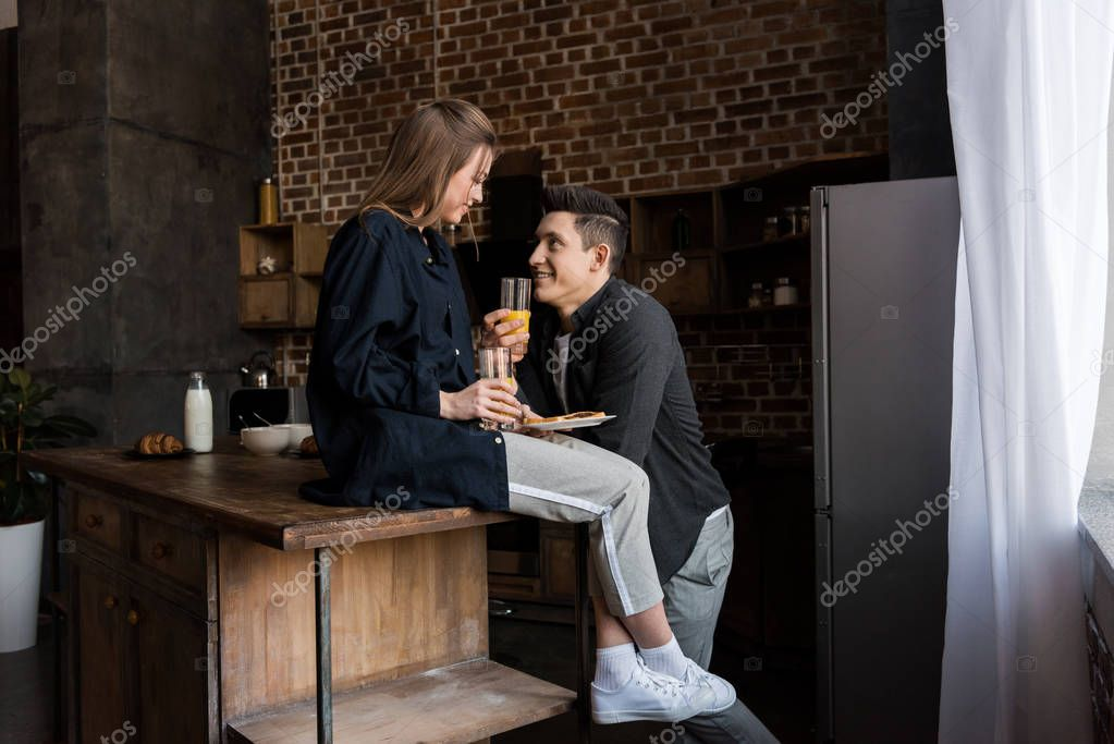 smiling couple with orange juice looking at each other at kitchen