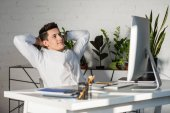 Photo smiling young businessman with hands behind head relaxing at workplace