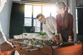 Fotografie young business partners playing table football together as team