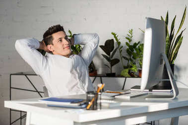 smiling young businessman with hands behind head relaxing at workplace