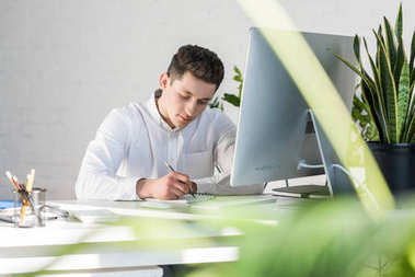 focused young businessman writing notes at workplace