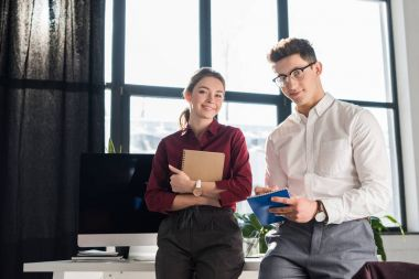 business partners leaning back on work desk and looking at camera
