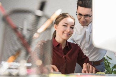 young handsome businessman flirtling with female colleague at office while she looking at camera