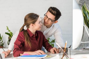 young handsome businessman flirtling with female colleague at workplace in modern office