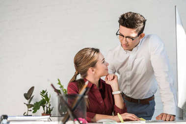 young handsome businessman flirtling with female colleague at office