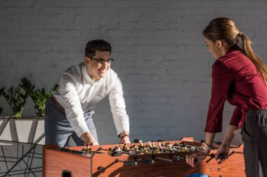 happy business partners playing table football at modern office