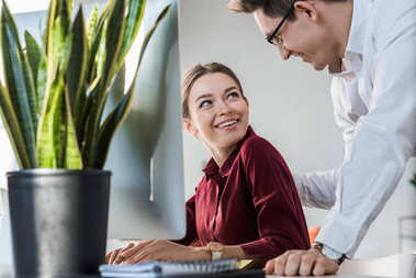 handsome businessman flirtling with female colleague at office