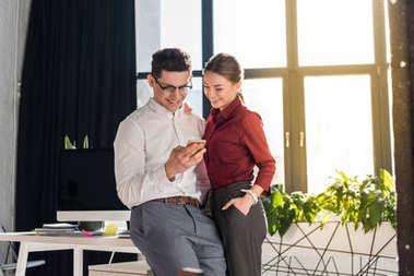happy businesspeople couple at modern office using smartphone together
