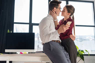 attractive kissing young couple in formal clothing at office