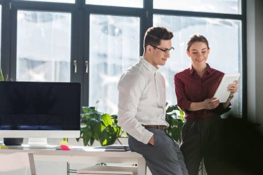 business partners looking at tablet together at workplace