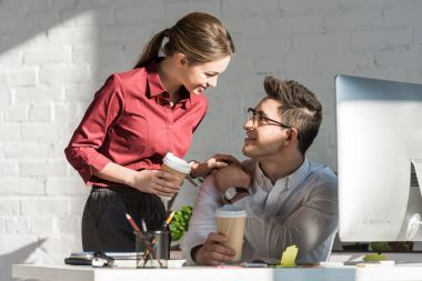happy young managers with coffee to go flirting at office