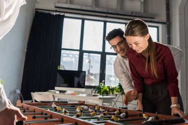 happy business partners playing table football together as team
