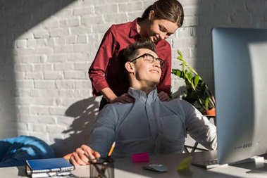 businessman recieving massage from his girlfriend at workplace
