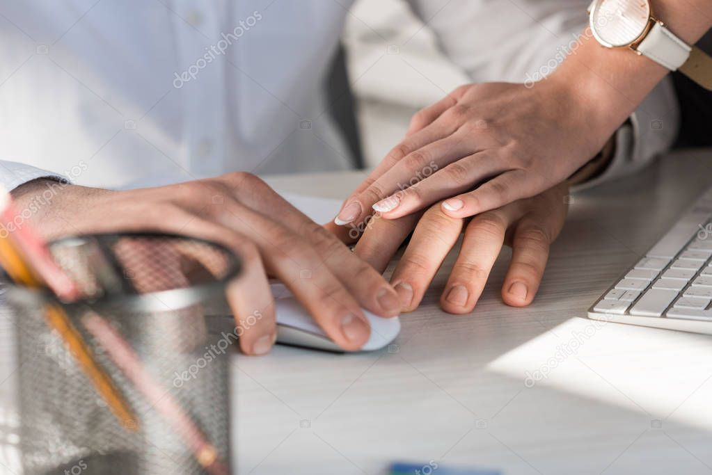 cropped shot of manageress holding hand of colleague at work