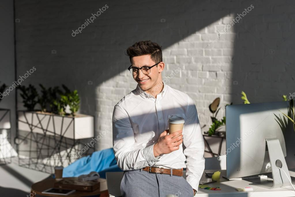smiling young businessman with paper cup of coffee at workplace