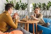 junges glückliches Paar beim Schachspielen auf Sitzsäcken