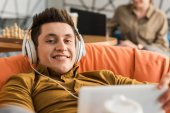 Photo smiling young man relaxing with tablet and headphones