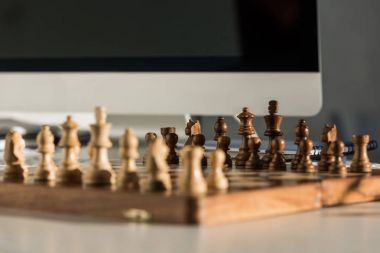 close-up shot of chess board at workplace near computer