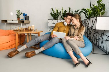 young couple cuddling using tablet together while sitting in bean bag