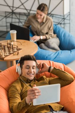 young man listening music with tablet and headphones while sitting in bean bag with blurred woman with laptop on background