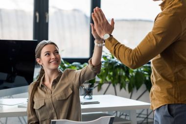 business partners giving high five at office