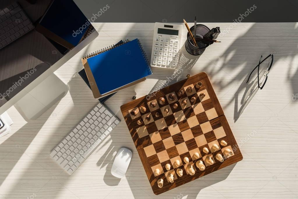 top view of chess board at workplace with computer