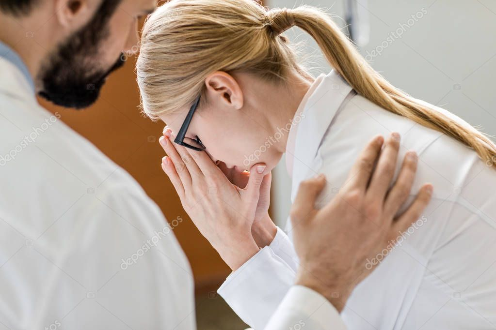 doctor soothing upset colleague