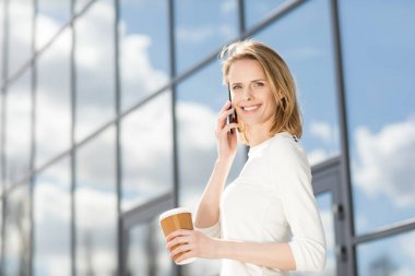 Young smiling woman with coffee and smartphone outdoors near office building stock vector