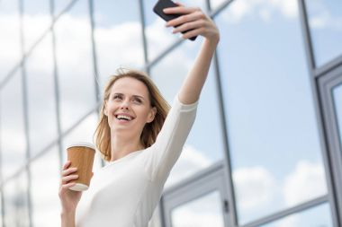 Young smiling woman with coffee taking selfie outdoors near office building stock vector