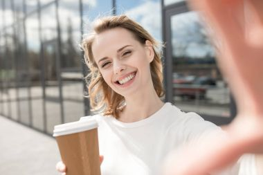 Young smiling woman with coffee taking selfie, Camera Point of View stock vector