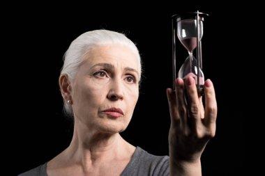 senior woman holding sand clock