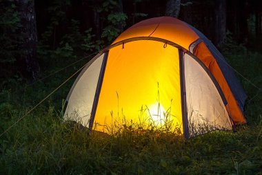 The light burns in the tent at night