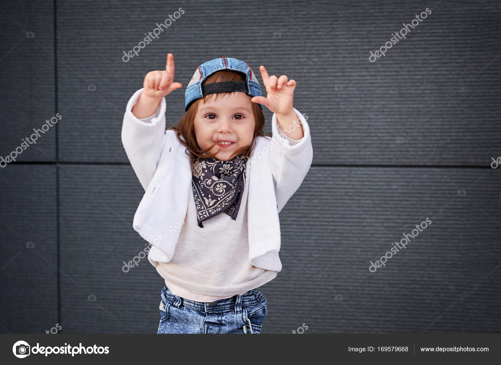 Portrait of a cute little girl in fashionable clothes.little baby girl in the  baseball cap happy dancing in the background of the gray wall. child waving  ... ee916b5ba539