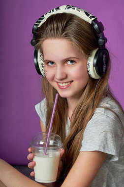 Teen girl loves to listen to the song with headphones.girl drinks smoothies