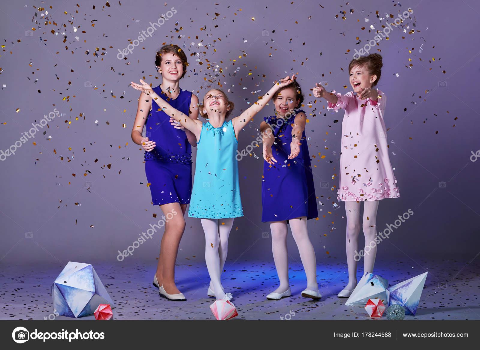 Gruppe von Kindern genießen Partei und werfen Konfetti. Mode ...