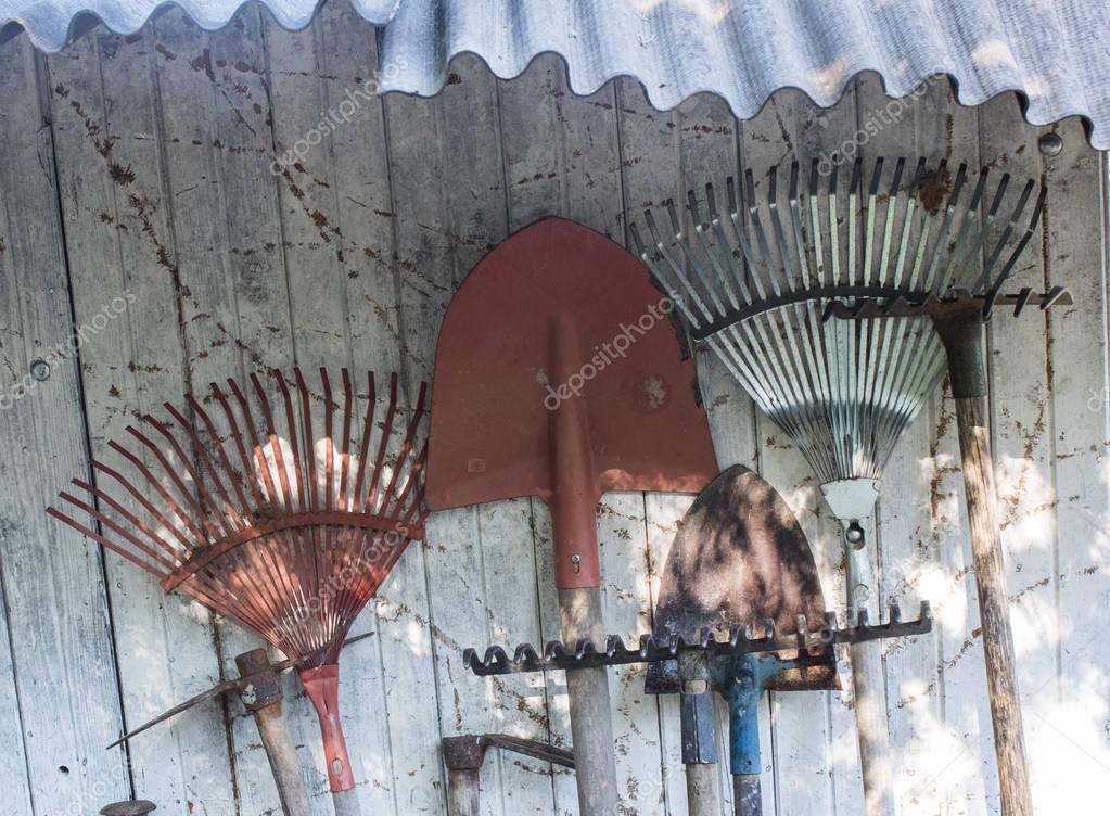Farmer's tools resting on the wall of a shed.