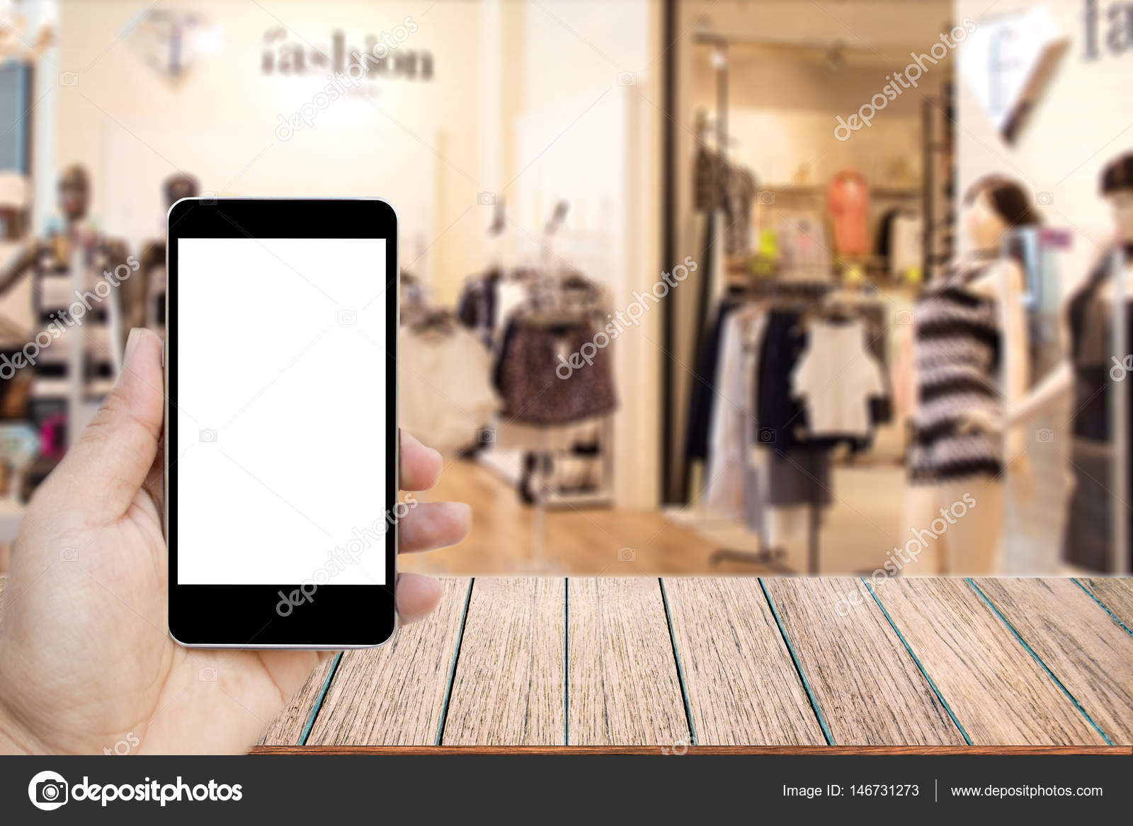 Mock up image of hand holding black mobile phone with blank white