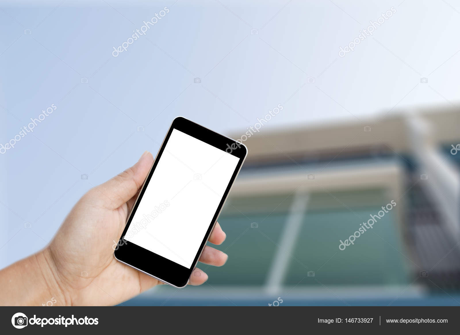 Hand holding black mobile phone with blank white screen